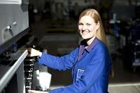 Kathrin arbeitet an einer Maschine und lächelt in die Kamera.
