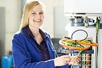 Kathrin hält ein Kabel in der Hand und lächelt freundlich in die Kamera.