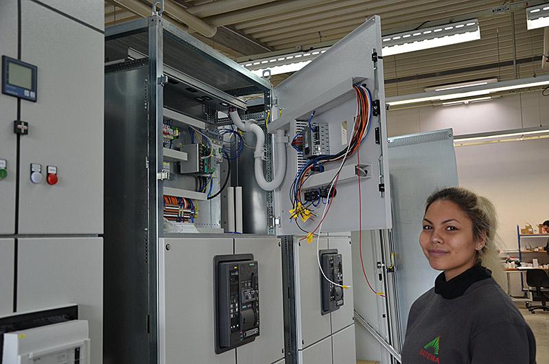Luana öffnet einen Schrank, der mit Kabeln ausgelegt ist.