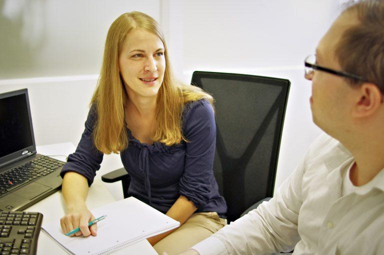 Patrizia unterhält sich am Schreibtisch mit einem Kollegen und hat neben Laptop und Tastatur einen Block mit Notizen vor sich liegen.