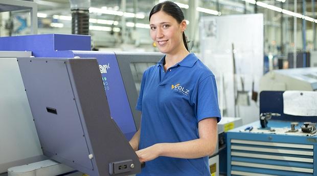 Die Zerspanungsmechanikerin Sandra Hübner bedient eine Maschine und lächelt dabei freundlich in die Kamera.