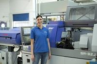 Sandra steht in Arbeitskleidung vor mehreren Maschinen.