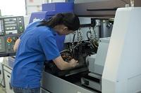 Sandra schraubt etwas an einer Maschine.