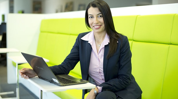 Die Informatikerin Sule Dogan sitzt auf einer Bank vor ihrem Laptop und lächelt in die Kamera.