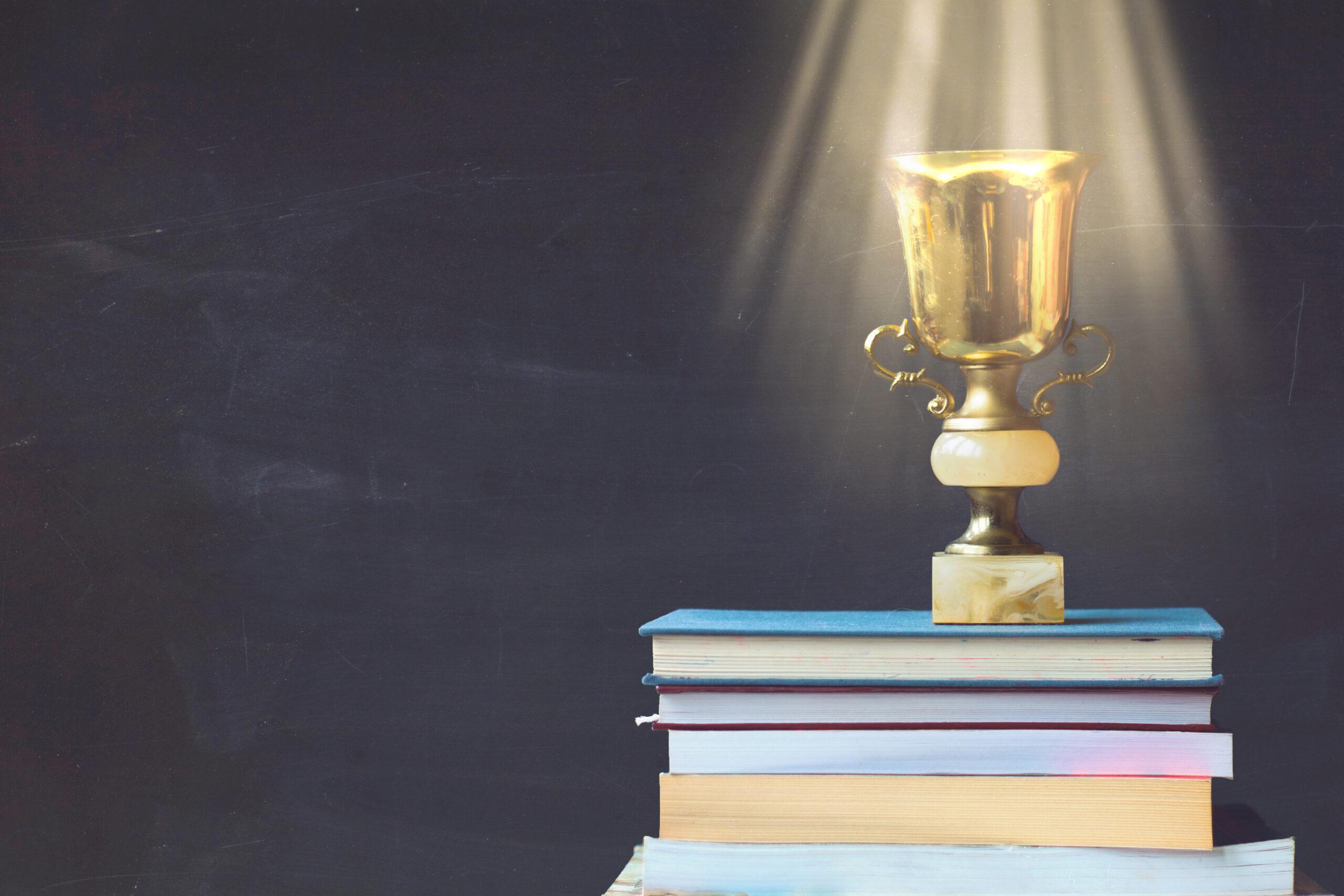 Ein Pokal auf einem Bücherstapel.
