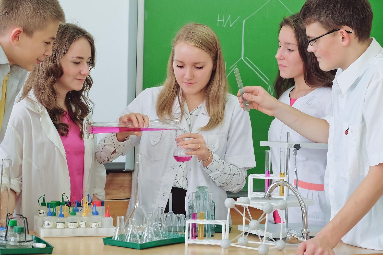 Fünf Schülerinnen und Schüler machen gemeinsam ein chemisches Experiment.