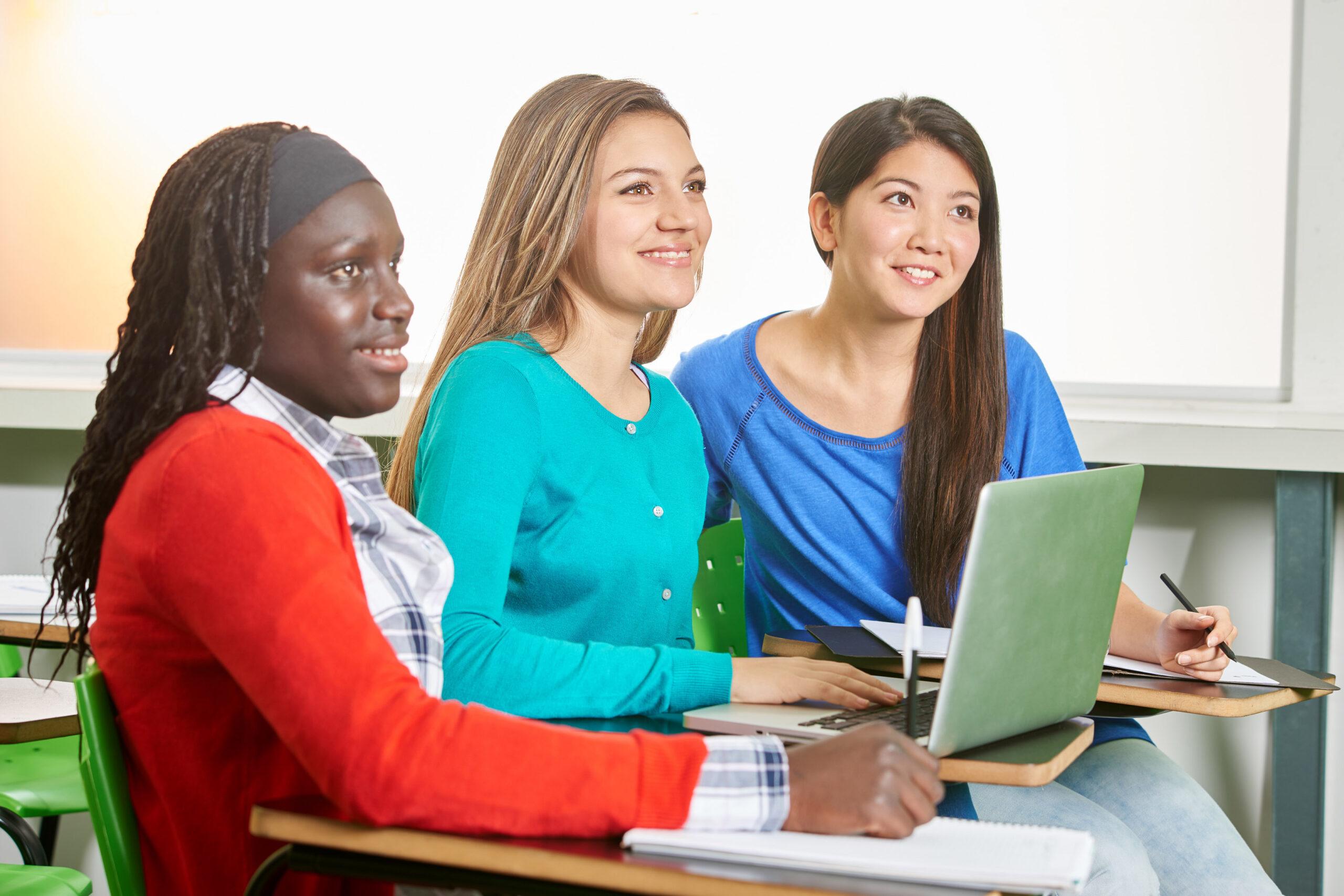 Drei Schülerinnen blickend gespannt und lächelnd nach vorne.
