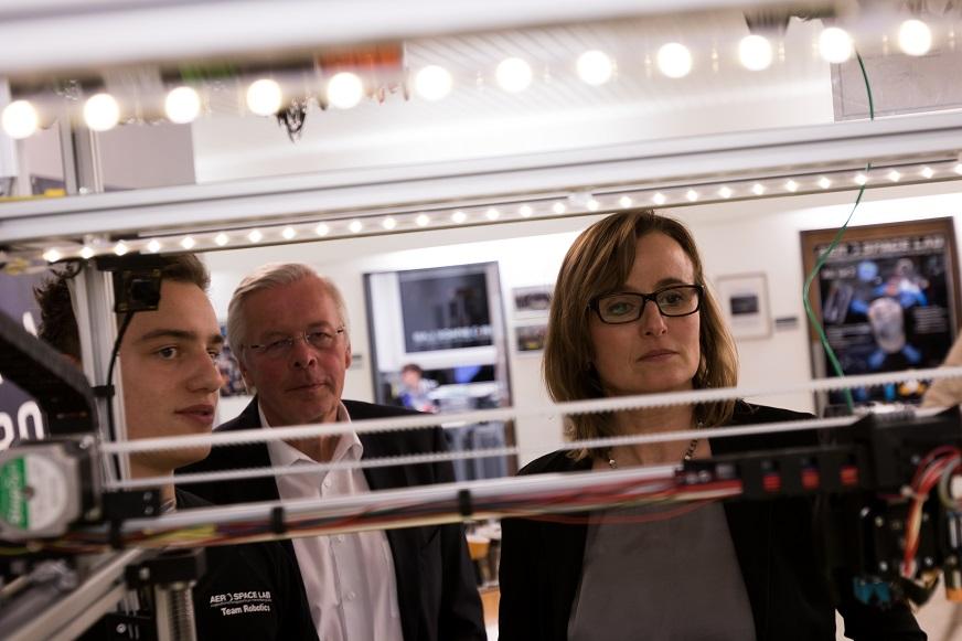 Die Staatssektretärin betrachtet mit zwei anderen Personen eine Gerätschaft im Aerospace-Lab.