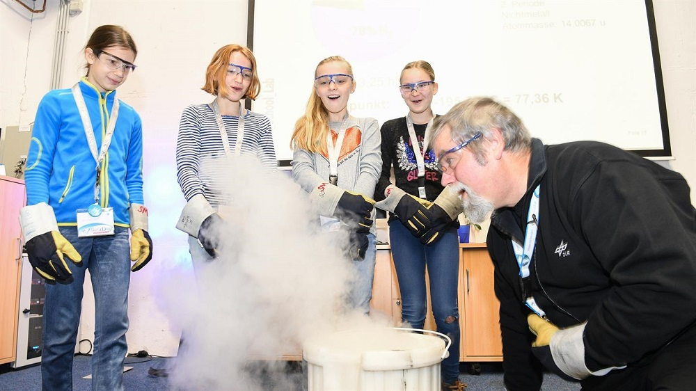 Vier Mädchen bestaunen ein rauchendes Experiment beim DLR