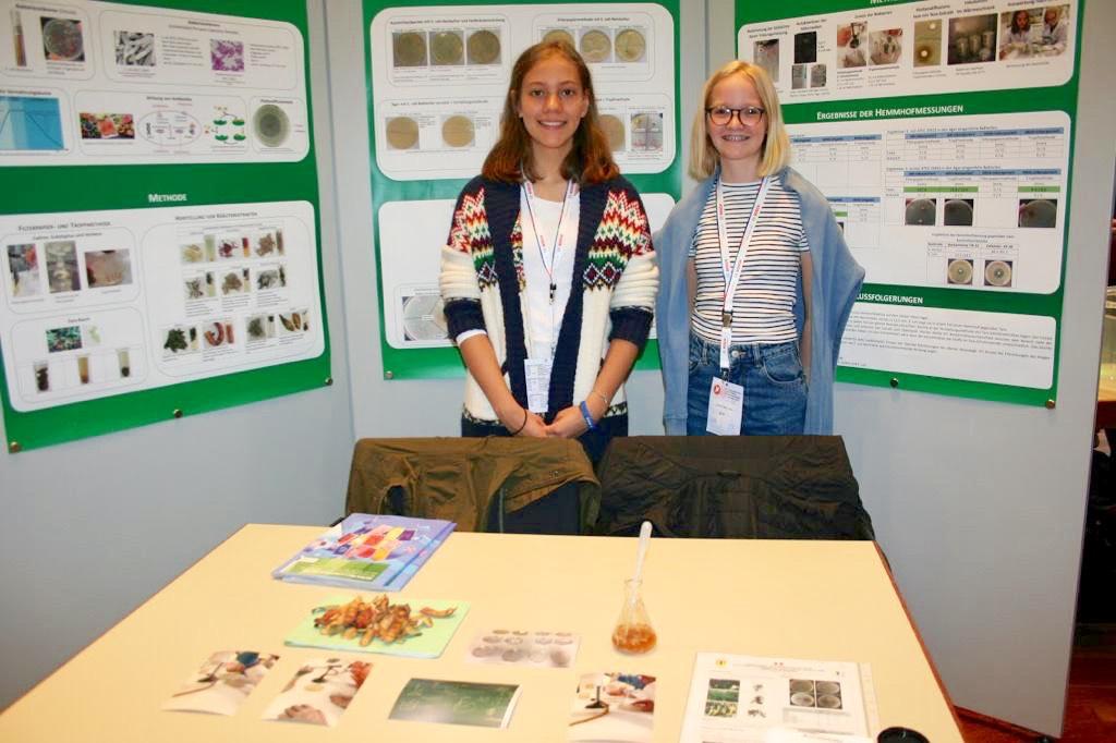 Zwei Teilnehmerinnen, die extra aus Peru angereist sind, präsentieren stolz ihren Beitrag zu Heilkräutern für Jugend forscht.