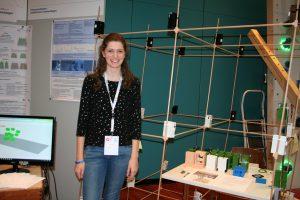 Die Landessiegerin Antonia steht neben einem Versuchsaufbau bei Jugend forscht.