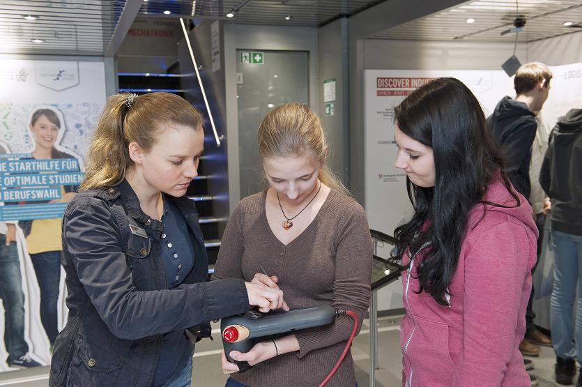 Bild einer Frau, die zwei interessierten Mädchen ein technisches Gerät zeigt.