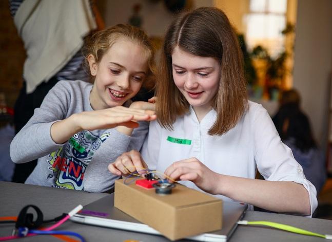 Zwei Mädchen bauen gemeinsam ein Elektrogerät