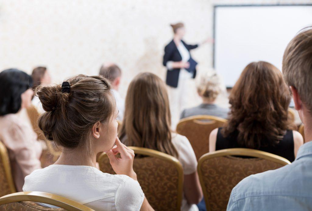 Bild einer beispielhaften Seminarsituation mit Blick aus dem Publikum nach vorne zum Vortragenden an einer Tafel.