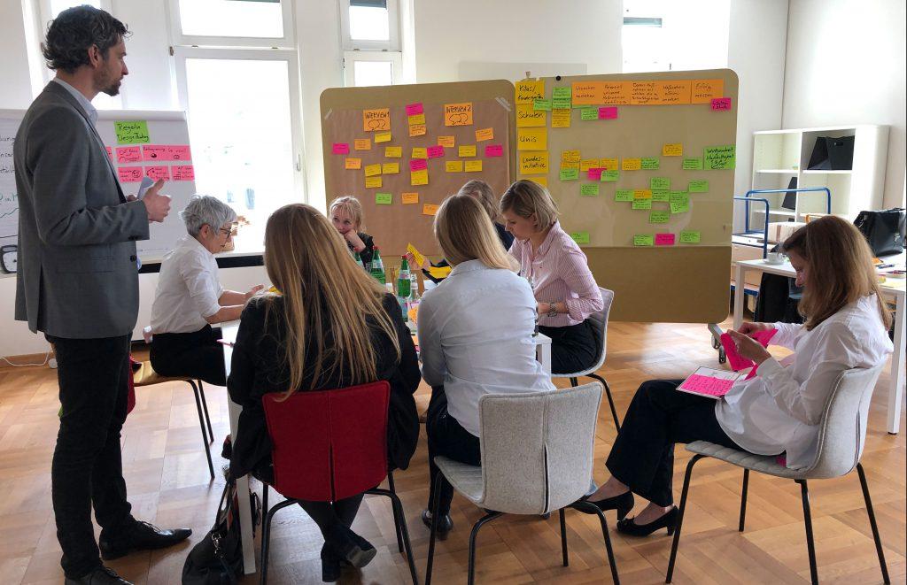 Eine Aufnahme der Teamarbeit beim Workshop zu Design Thinking, wo die Teilnehmer konzentriert an einem Tisch sitzen.