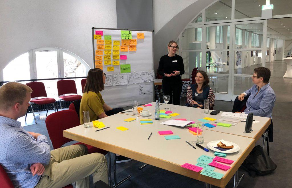 Eine Fotografie des gemeinsamen Brainstormings beim Design Thinking Workshop mit Teilnehmern an einem Tisch neben einem Whiteboard mit bunten Karten.