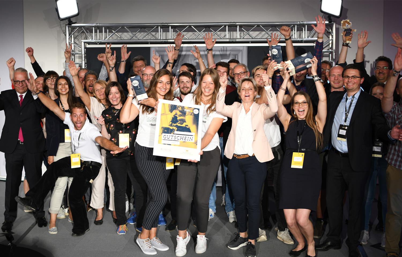 Die Mitarbeiter und Gründer des Unternehmens Spoontainable stehen mit dem Preis auf der Bühne und jubeln gemeinsam mit der Wirtschaftsministerin Dr. Nicole Hoffmeister-Kraut über ihren Sieg.