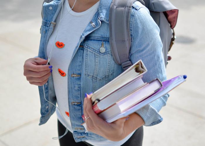 Ein Mädchen hält einen Bücherstapel fest unter den Arm geklemmt und trägt einen Rucksack auf dem Rücken.