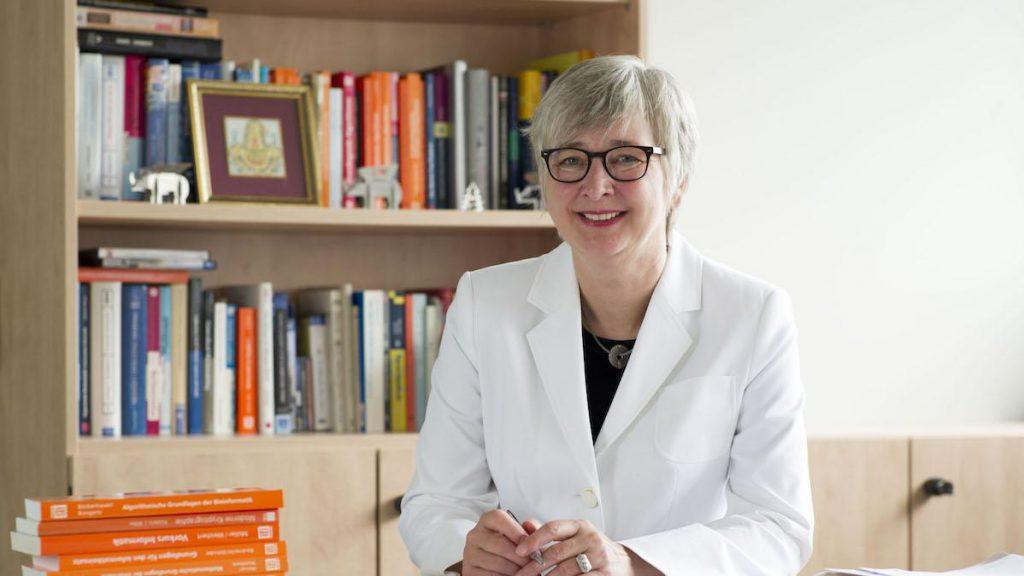 Dorothea Wagner steht in einem weißen Laborkittel vor einem Bücherregal und lächelt in die Kamera.