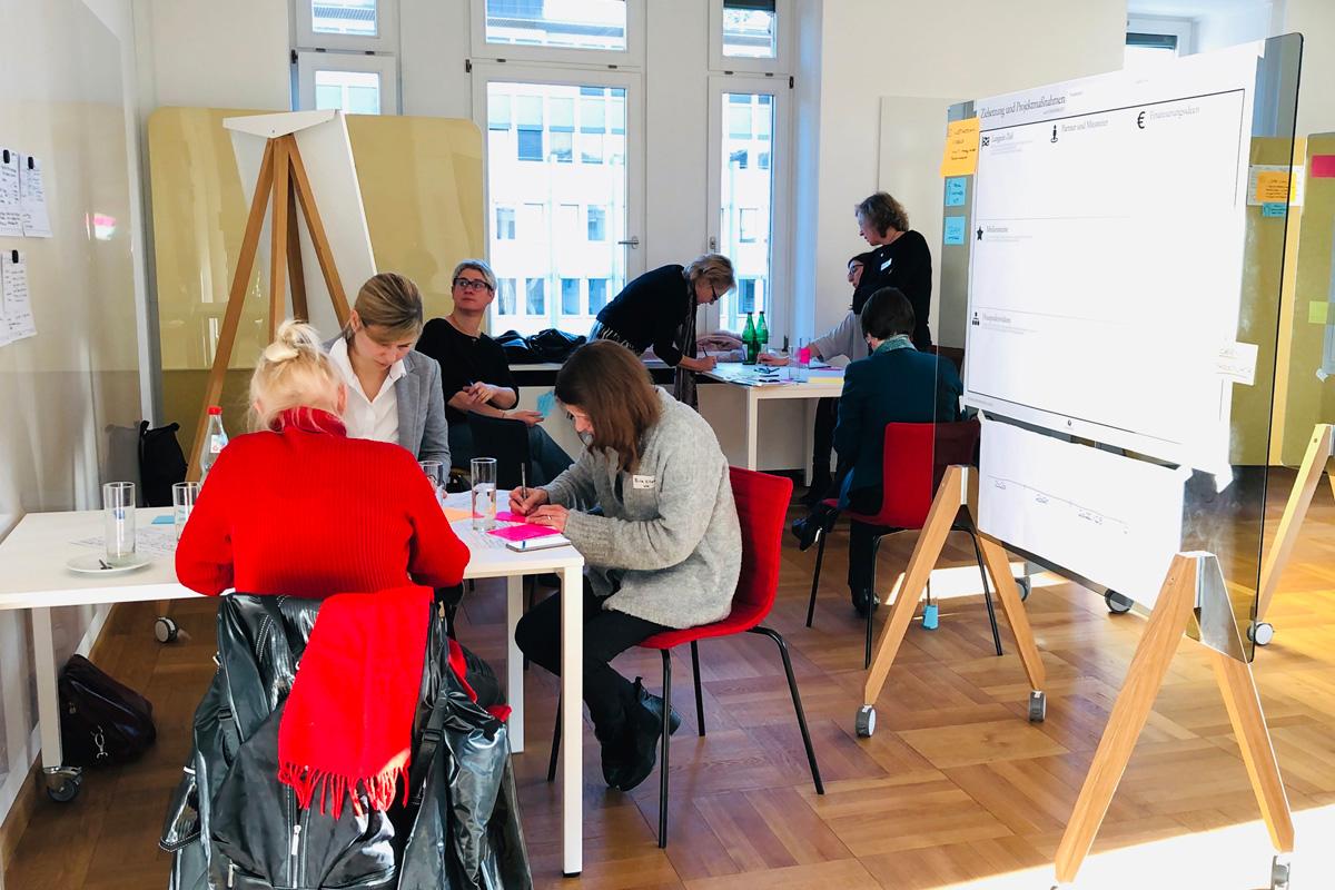 Personen sitzen in Gruppen an Tischen und arbeiten Ergebnisse aus.