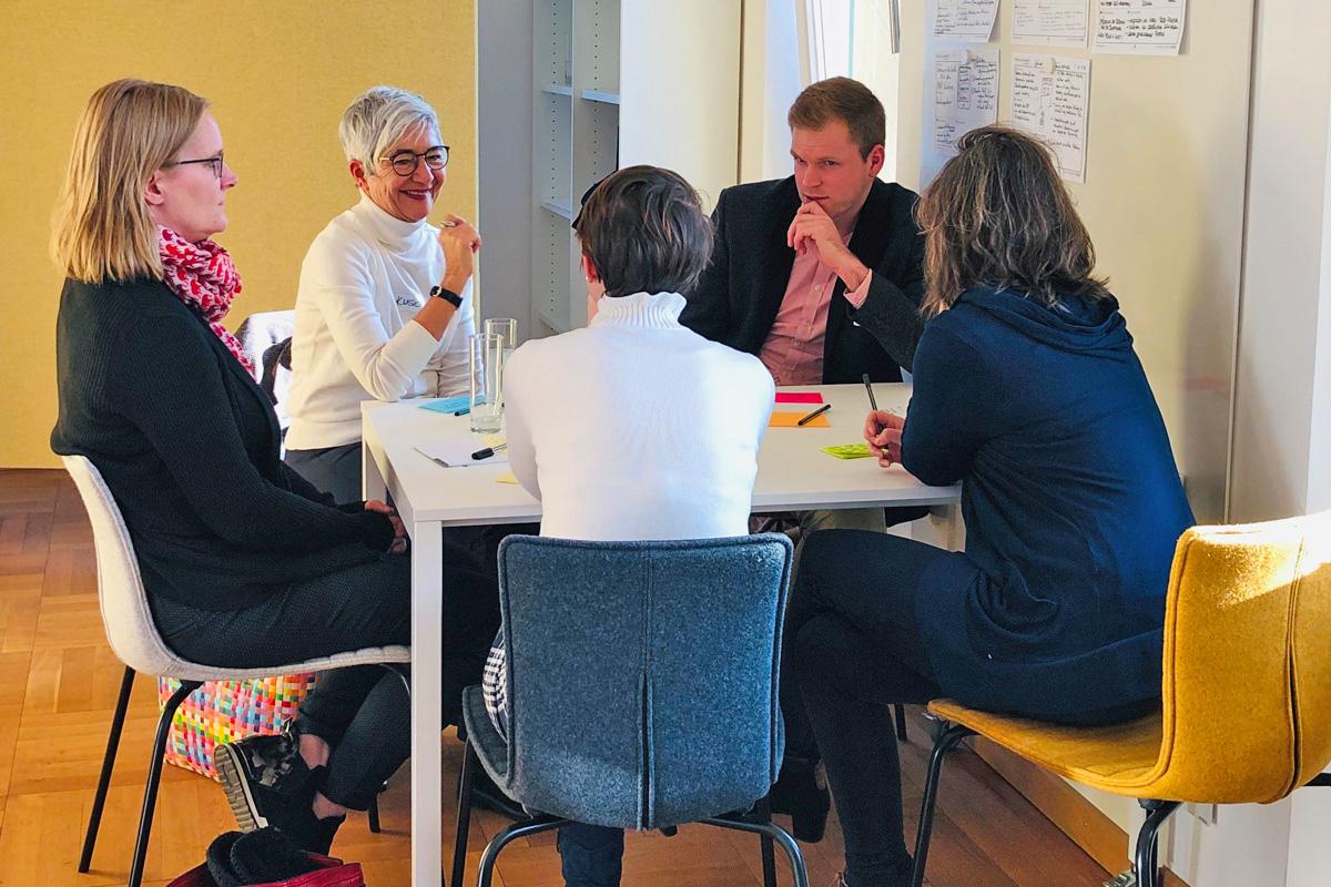 Eine Gruppe von Personen unterhält sich an einem Tisch und notiert die Ergebnisse auf bunten Karten.
