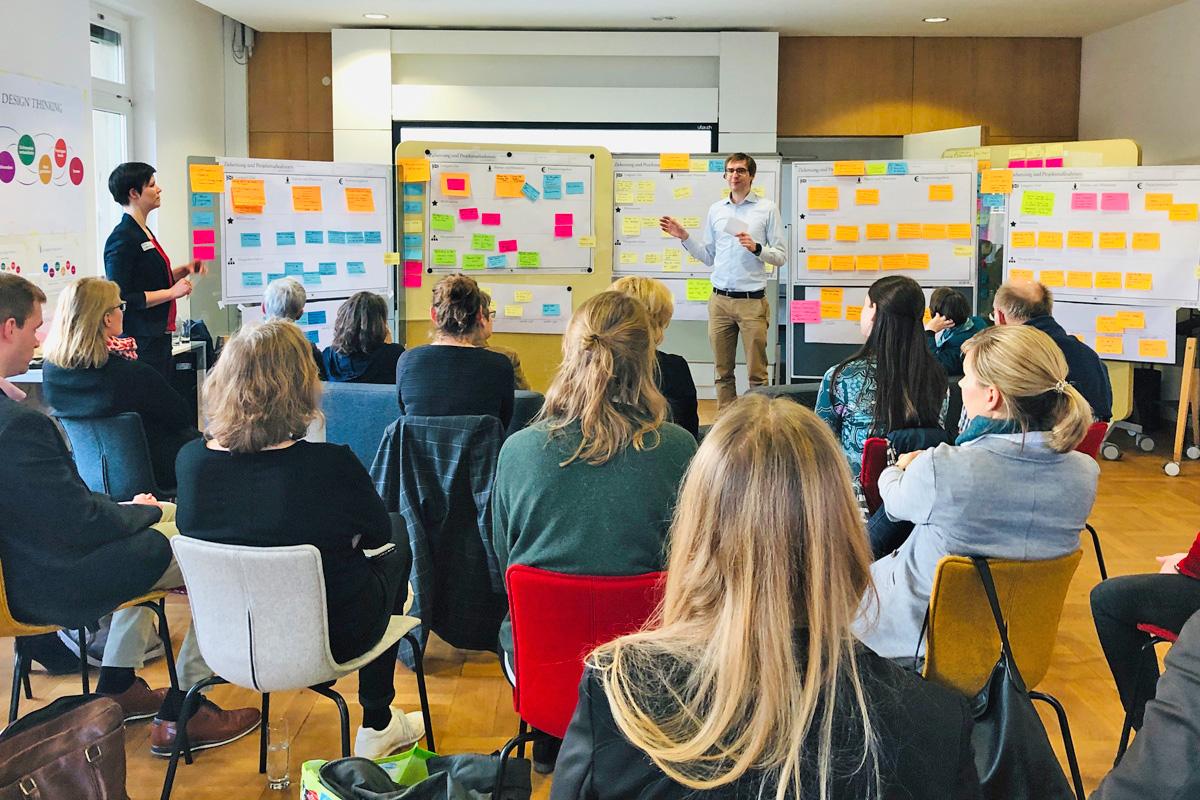 Zwei Personen berichten den anderen Workshopteilnehmern mit Hilfe von beklebten Tafeln die herausgearbeiteten Ergebnisse.