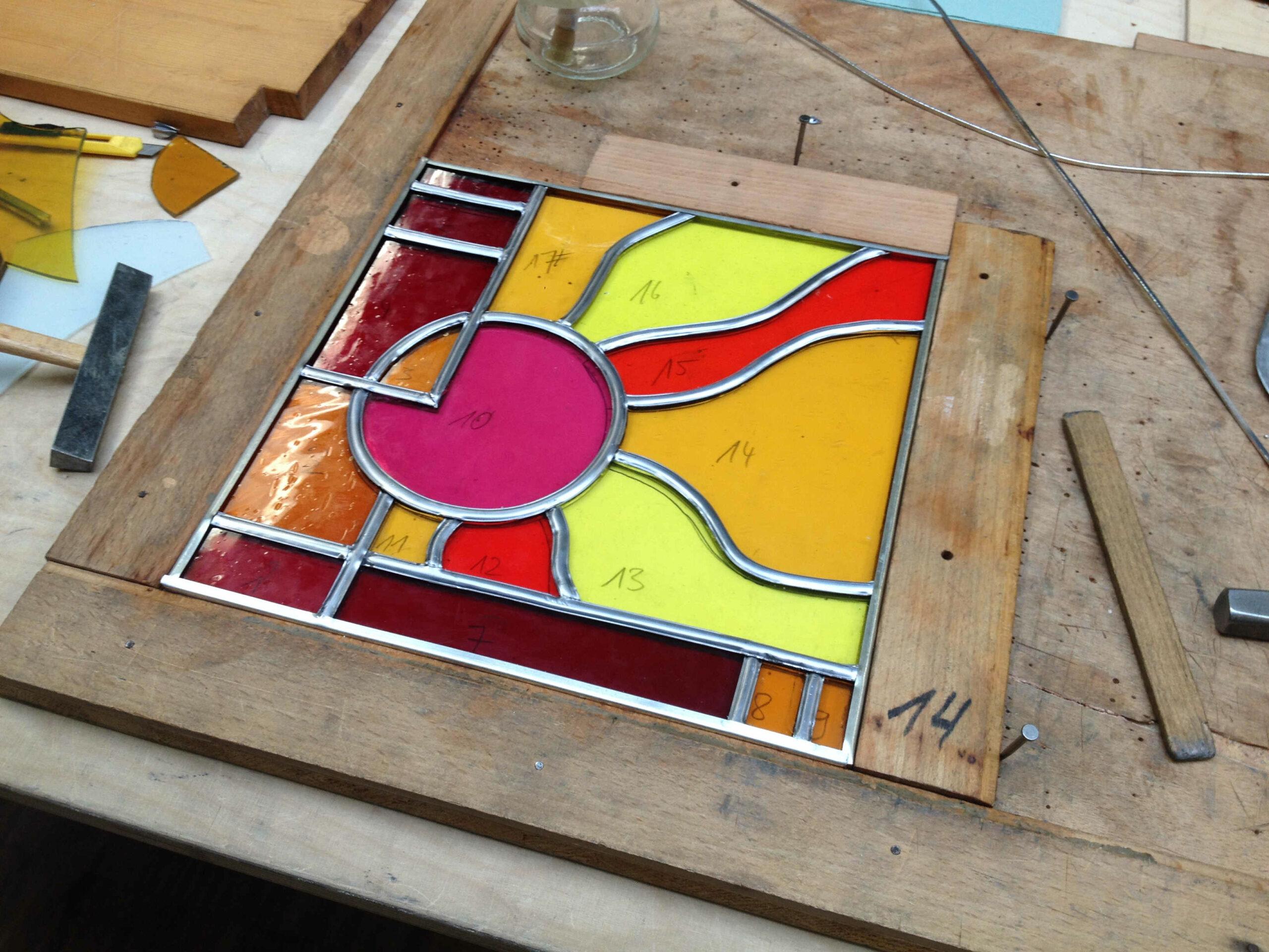 Ein buntes Bleiglasfenster in Rot- und Gelbtönen.