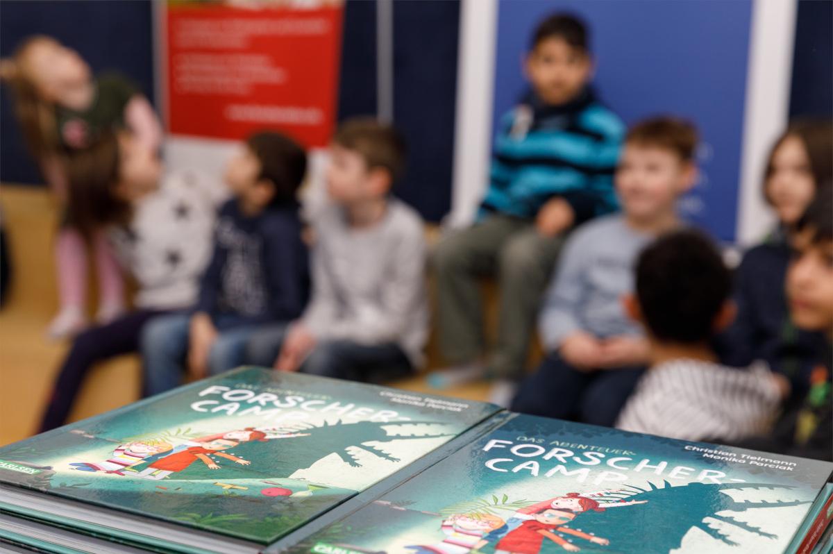 Bei der Buchvorstellung des Jugendbuchs sitzen die Kinder in einem Stuhlkreis.