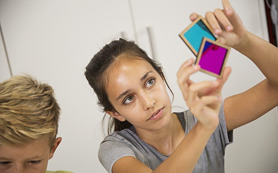 Mädchen hält zwei Farbplatten übereinander