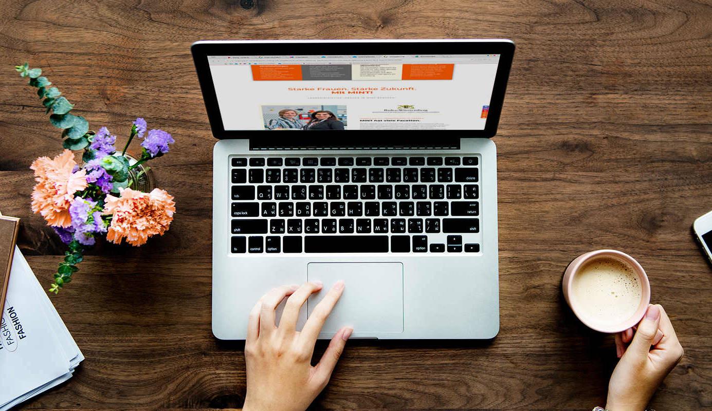 Ein aufgeklappter Laptop, der die MINT-Homepage aufgerufen hat steht auf einem Tisch.