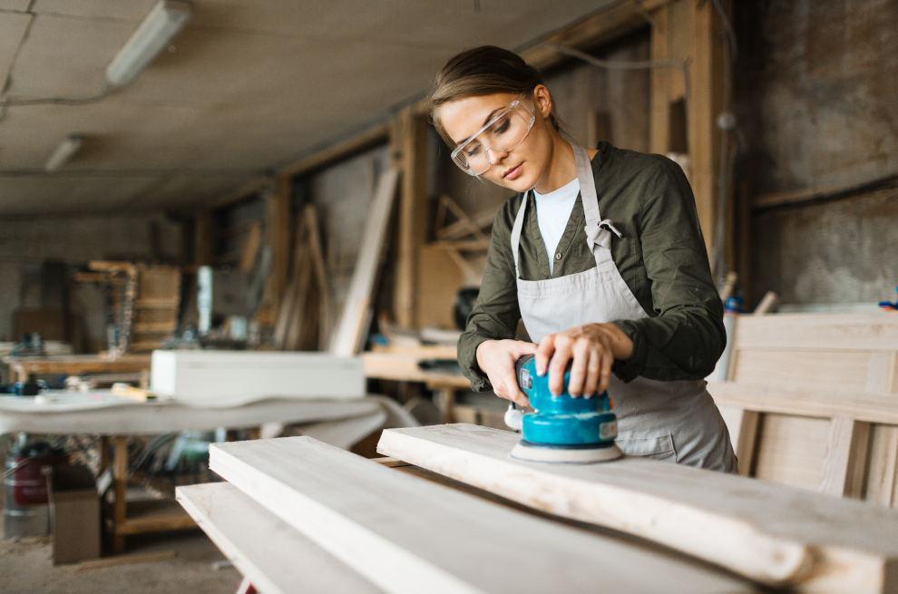 Junge Frau ist in einer Werkstatt und schleift mit einer Maschine Holz