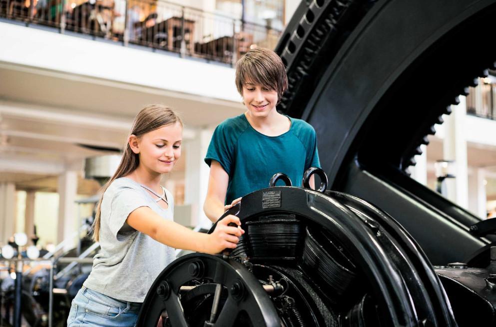 Ein Junge und ein Mädchen sehen sich eine alte Maschine genauer an.