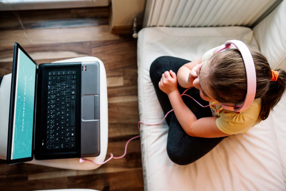 Mädchen sitzt mit Kopfhörern vor einem Laptop
