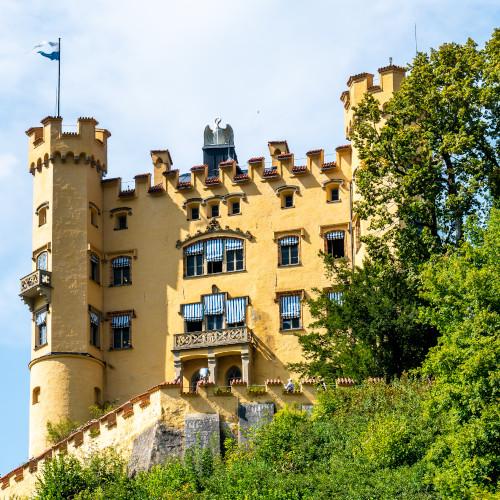Ein Blick auf das Schloss Hohenschwangau mit blau-weiß-gestreiften Markisentüchern an den Fenstern.
