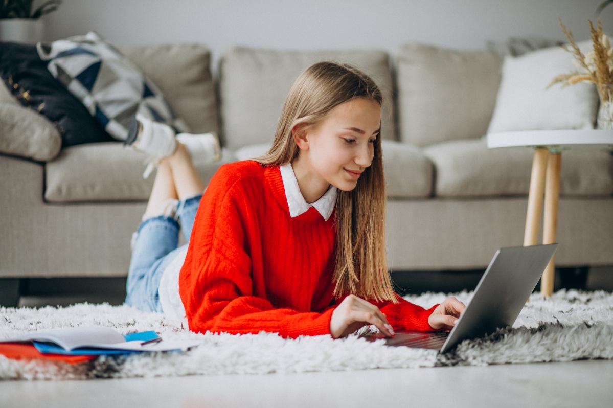 Mädchen liegt auf dem Bauch und arbeitet an ihrem Laptop