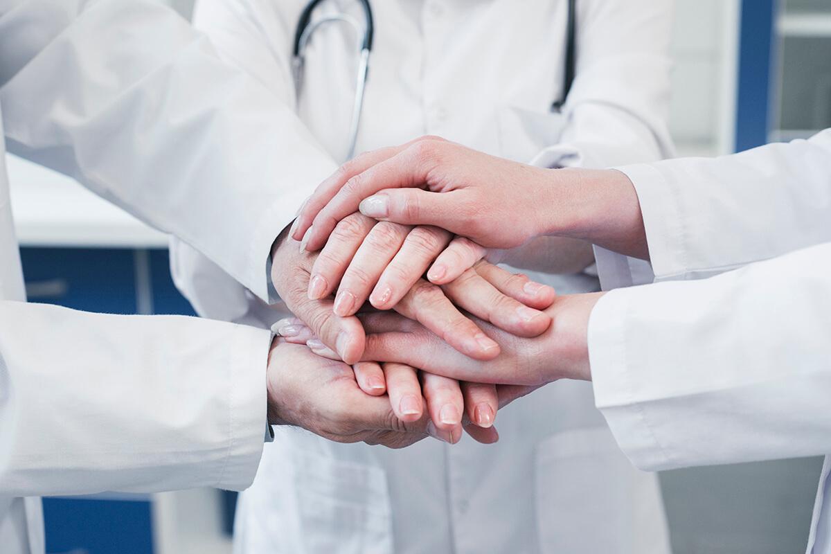 Mehrere Ärzte legen die Händer übereinander.