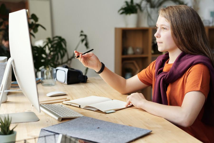 Ein Mädchen sitzt vor einem Computer und macht sich Notizen.