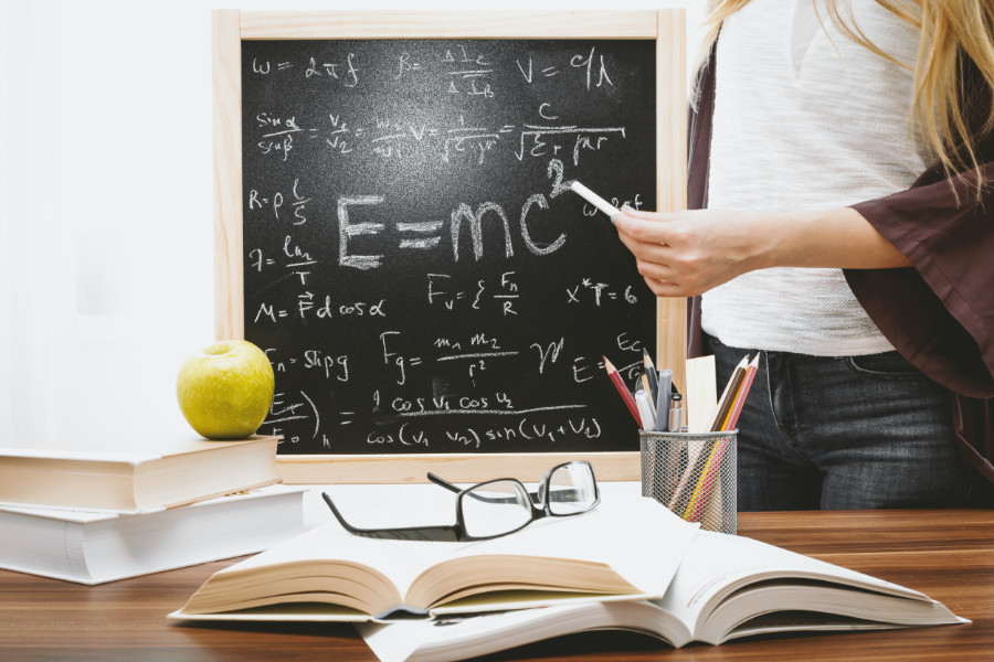 Ein Mädchen schreibt eine mathematische Formeln an eine Tafel.
