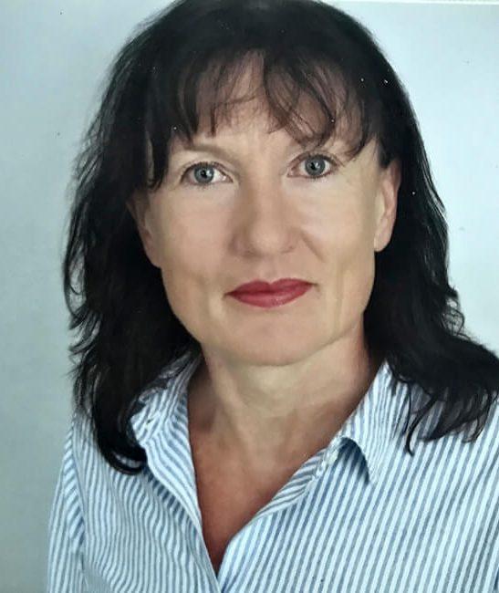 Die Hygienefachkraft Beate Schöneck blickt freundlich lächelnd in die Kamera. Sie hat schwarze Haare und trägt dunkelroten Lippenstift und eine weiß-blau-gestreifte Bluse.
