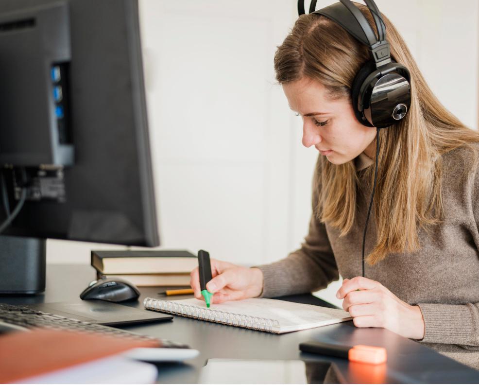 Mädchen sitzt mit Kopfhörern vor dem Bildschirm und nutzt e-leaning.