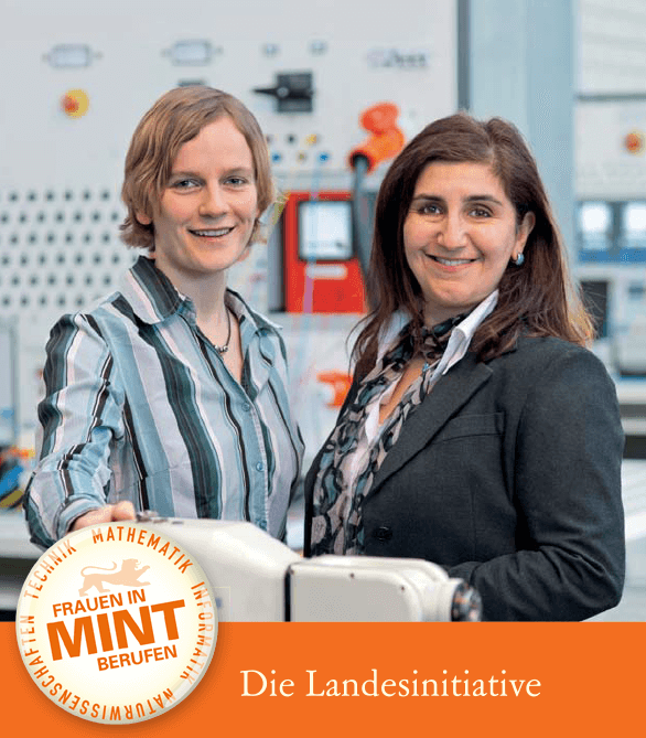 Zwei Wissenschaftlerinnen aus dem MINT-Bereich stehen vor einer Schalttafel und lächeln in die Kamera.