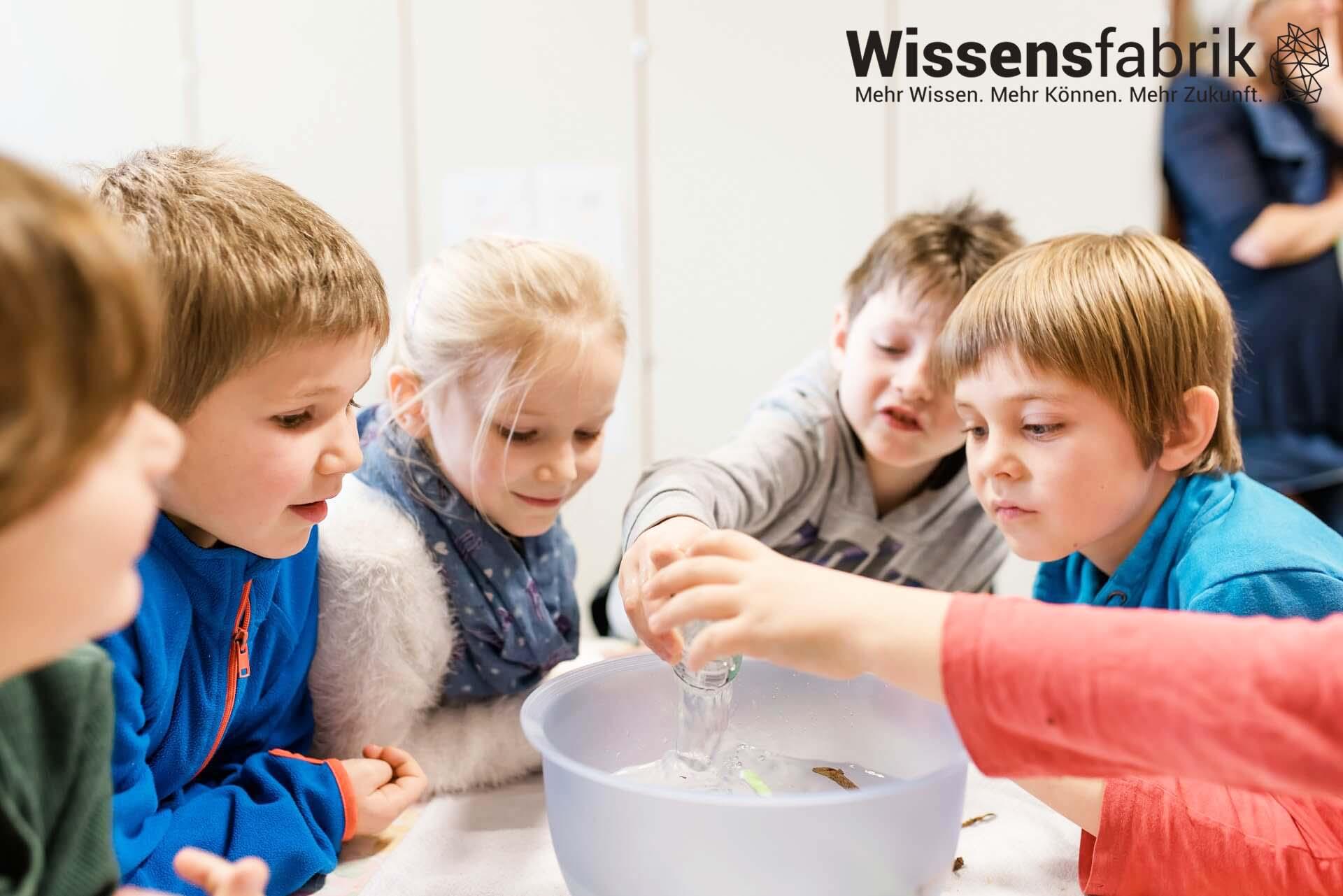 Kinder sitzen an einem Tisch und führen fröhlich ein Experiment durch.