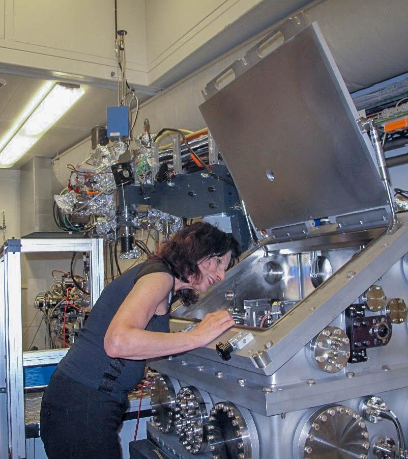 Gisela Schütz steht vor einer Maschine und untersucht die technischen Komponenten.