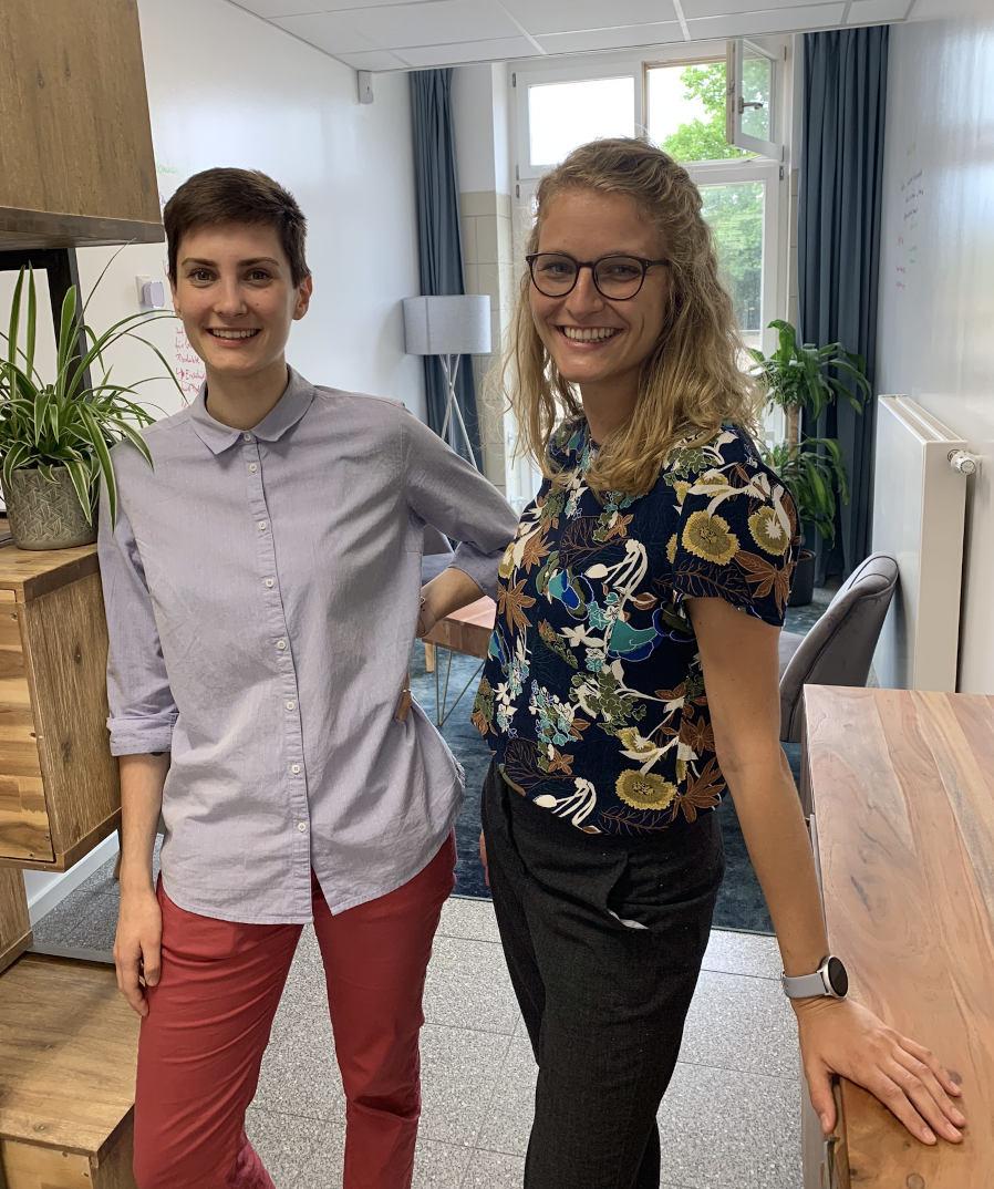 Maria Stepanov und Franziska Schneider stehen im Eingagsbereich der Ameria AG und lächeln in die Kamera.