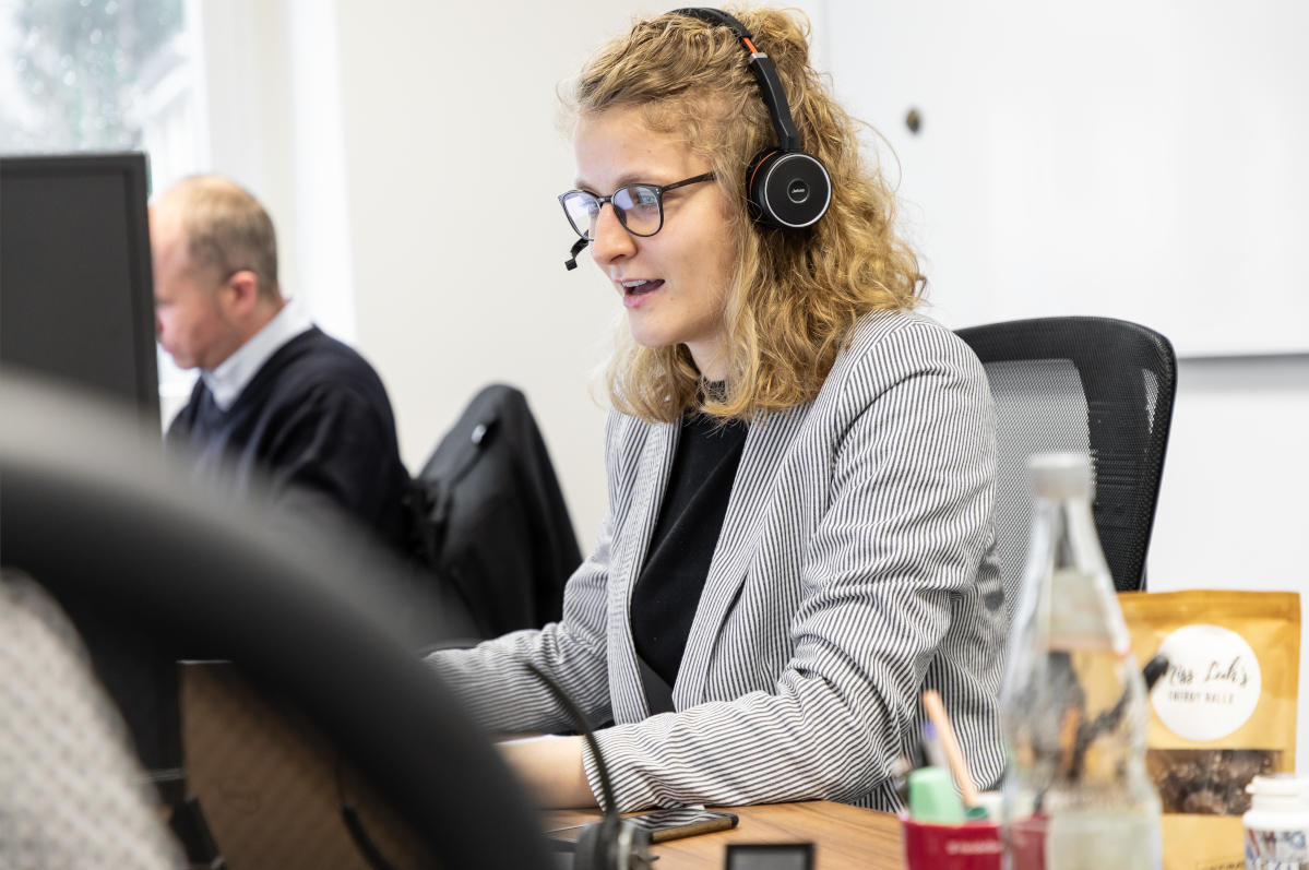 Franziska Schneider sitzt am Computer und trägt ein Headset.