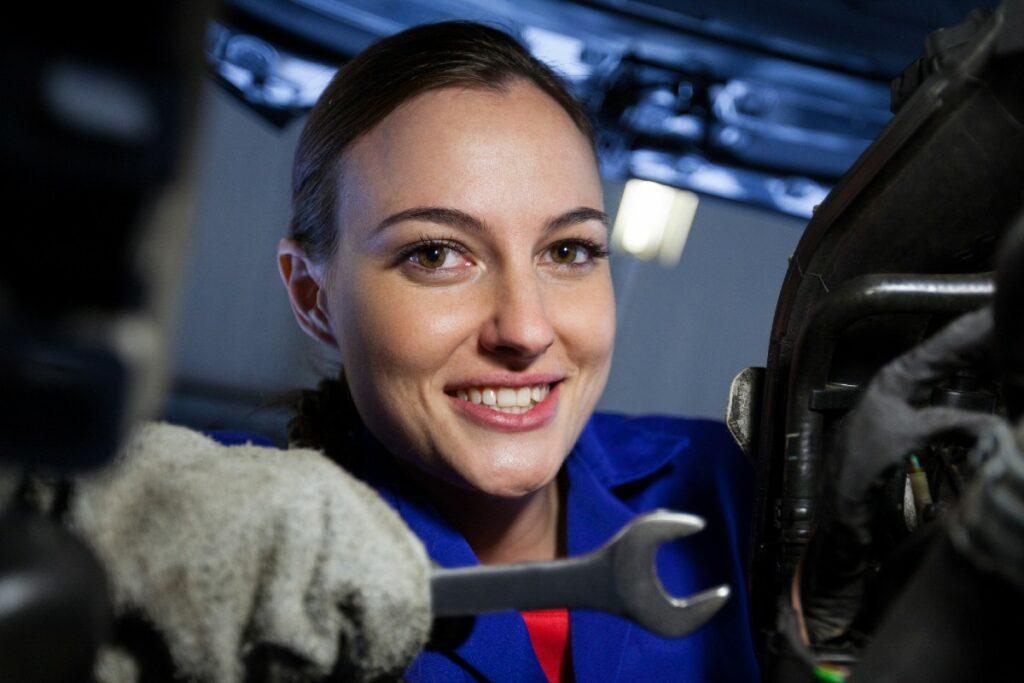 Das Bild zeigt eine junge Frau im Blaumann mit Schraubenschlüssel