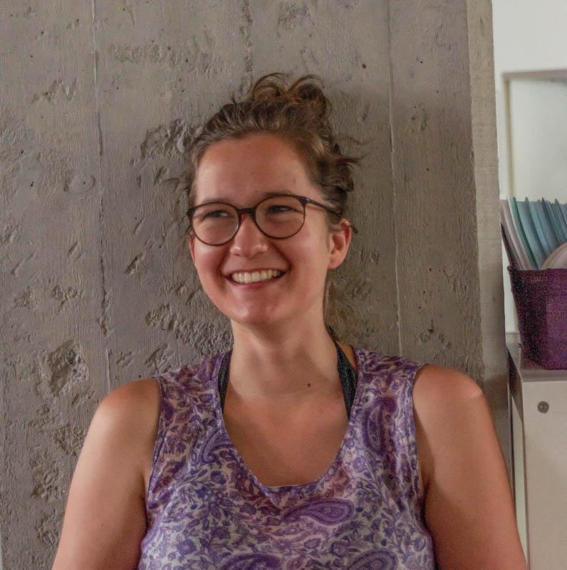 Lucia Parbel, Studentin der Agrarwissenschaften, lehnt an einer Steinmauer und lacht jemanden freundlich an.