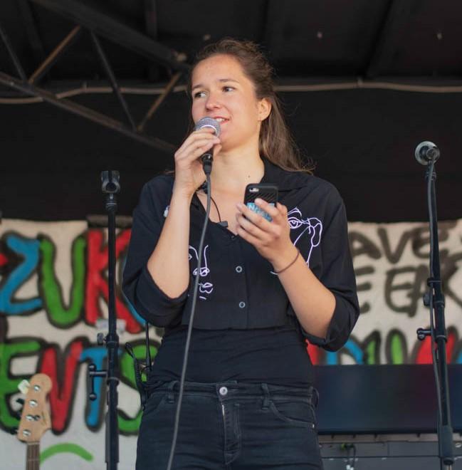 Lucia Parbel, Studentin der Agrarwissenschaften, steht auf einer Bühne einer Klima-Demo und spricht in ein Mikrofon.