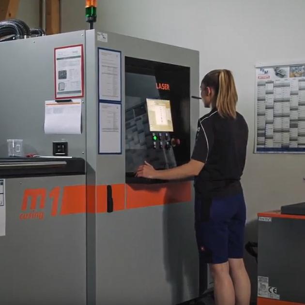 Isabel Koschmieder steht an einer Maschine und bedient sie.