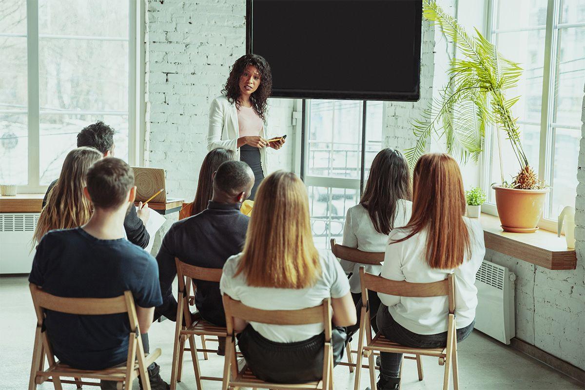 Mit Klick auf dieses Foto, welches mehrere Personen zeigt, die dem Vortrag einer Person zuhören, gelangen Sie zum Beitrag über Fortbildungsangebote für Lehrer an weiterführenden Schulen.